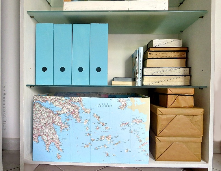painted magazine files, boxes wrapped in brown paper, and a cardboard box decoupaged with maps, Pretty and Practical Bookcases the Easy Way www.theboondocksblog.com
