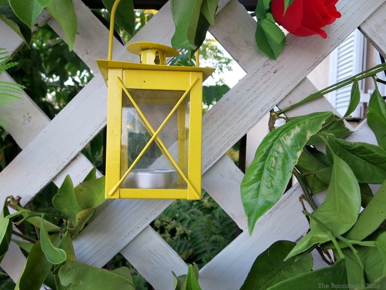 yellow lantern, Make an Easy Colorful Fence with Dollar Store Flowers www.theboondocksblog.com
