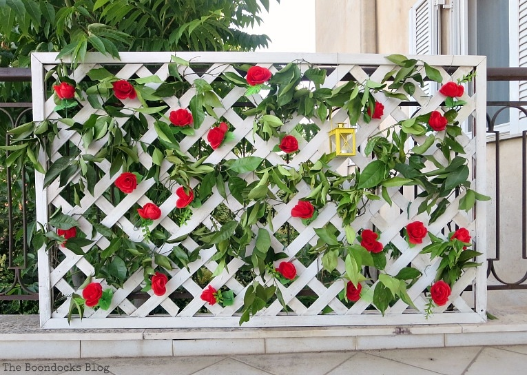 Finished panel with faux roses and lantern, Make an Easy Colorful Fence with Dollar Store Flowers www.theboondocksblog.com