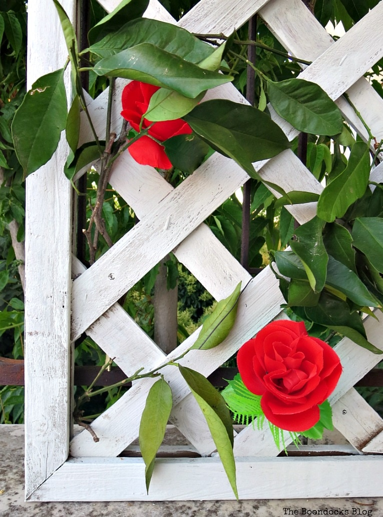 flowers peeking through green leaves, Make an Easy Colorful Fence with Dollar Store Flowers www.theboondocksblog.com