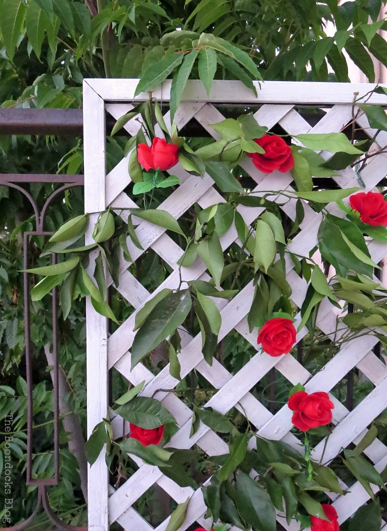 corner view of lattice with flowers and greenery, Make an Easy Colorful Fence with Dollar Store Flowers www.theboondocksblog.com