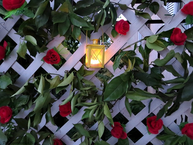 Lit tea light lantern on lattice fence, Make an Easy Colorful Fence with Dollar Store Flowers www.theboondocksblog.com