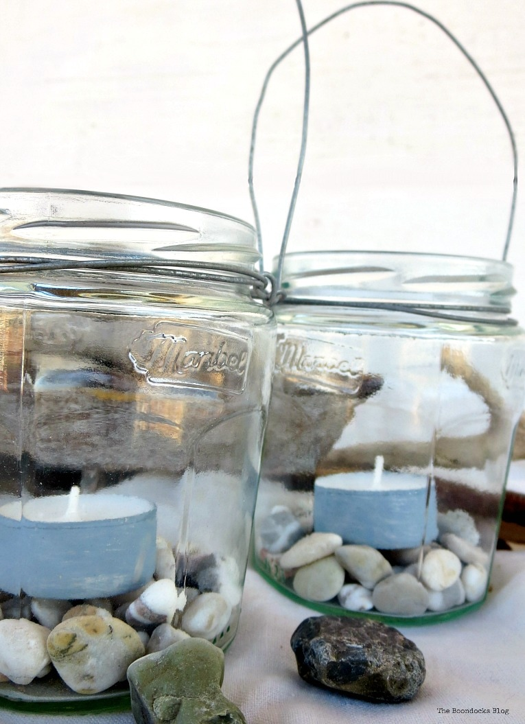 2 lantern jars with tea lights and pebbles inside, #easycraft #repurposedjars #tealightlanterns #fastcraft #DIYlanternlights #wireproject How to make Simple Lanterns with Repurposed Jars, www.theboondocksblog.com