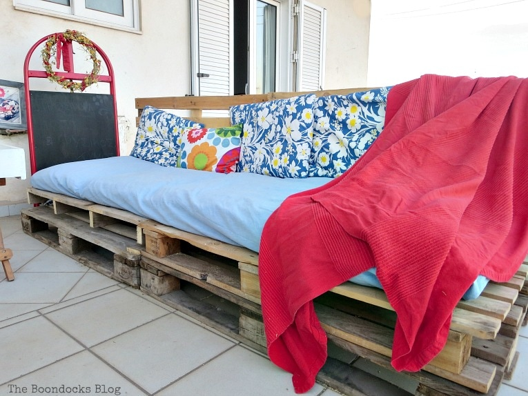 couch made from pallets, with fabric tucked in, Quickly Make a Super Easy Pallet Couch www.theboondocksblog.com