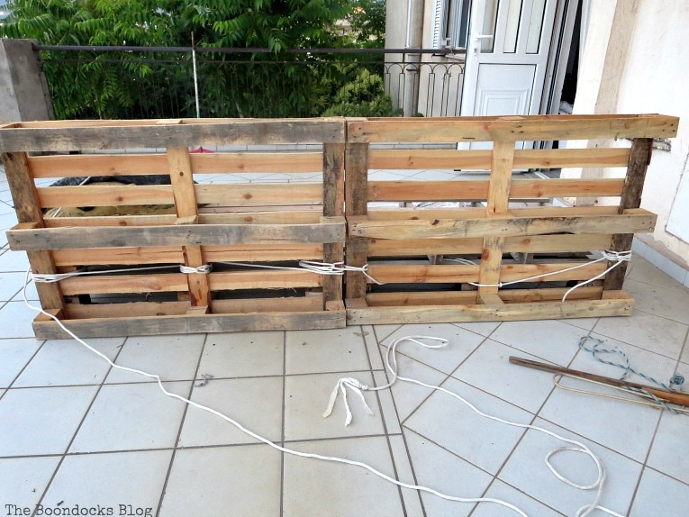 view of the tied vertical pallets, Quickly Make a Super Easy Pallet Couch www.theboondocksblog.com
