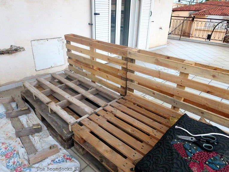 front view of pallets, Quickly Make a Super Easy Pallet Couch www.theboondocksblog.com