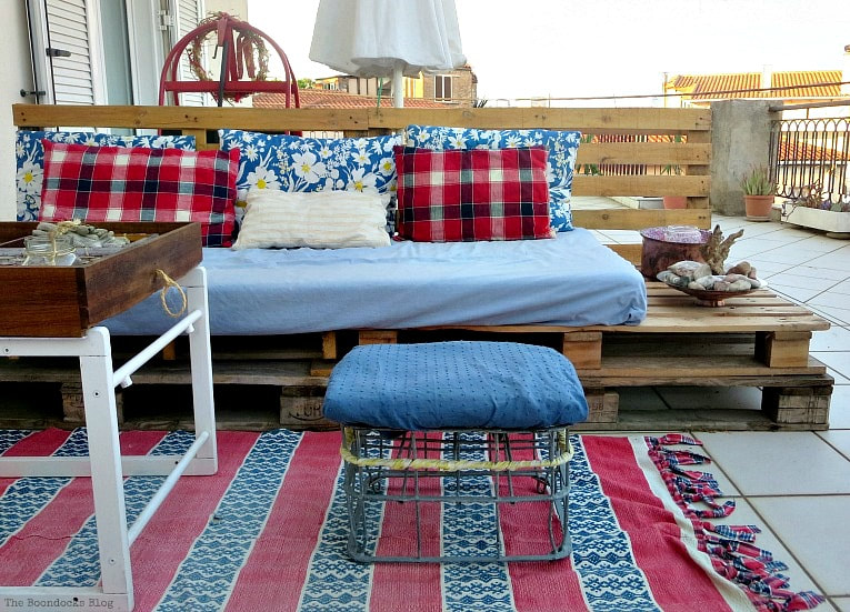 the pallet couch and space next to the seating, How to Decorate a Balcony with Re-Purposed Treasures, www.theboondocksblog.com