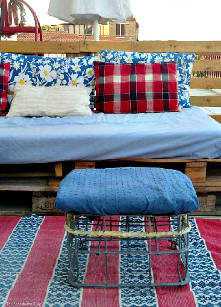 pallet couch with pillows and vintage milk crate stool, How to Decorate a Balcony with Re-Purposed Treasures, www.theboondocksblog.com