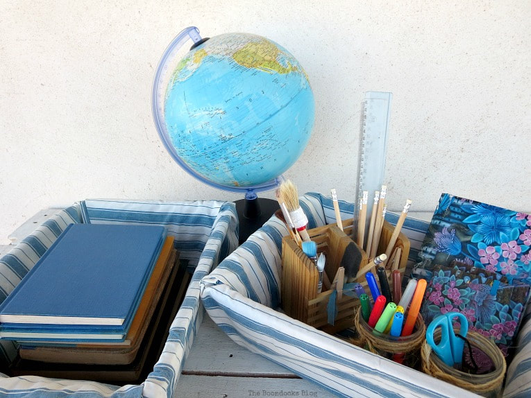 Baskets full of school supplies and books, placed next to a globe.