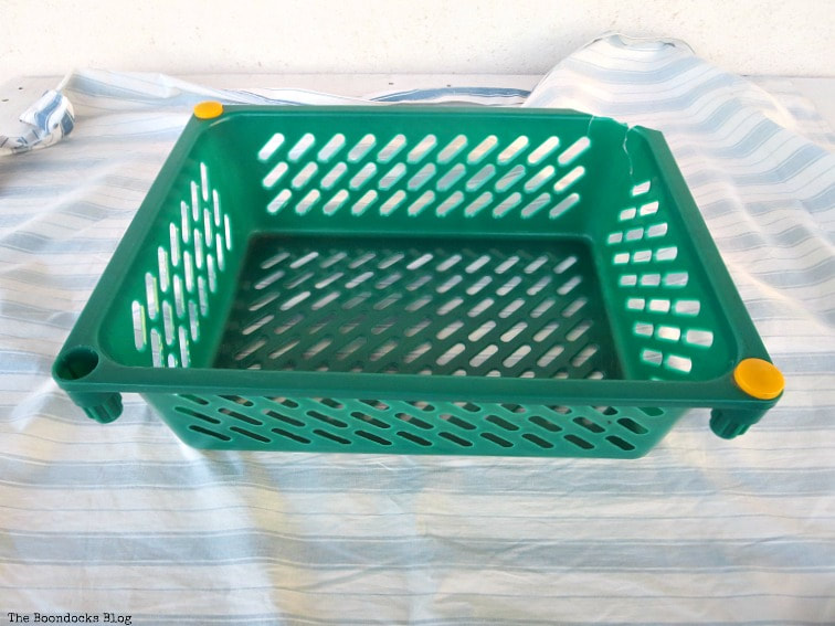 placing the fabric under the basket, How to Easily Upcycle Broken Plastic Baskets www.theboondocksblog.com