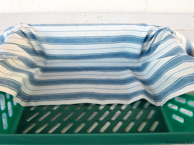 folding the fabric over the basket, How to Easily Upcycle Broken Plastic Baskets www.theboondocksblog.com