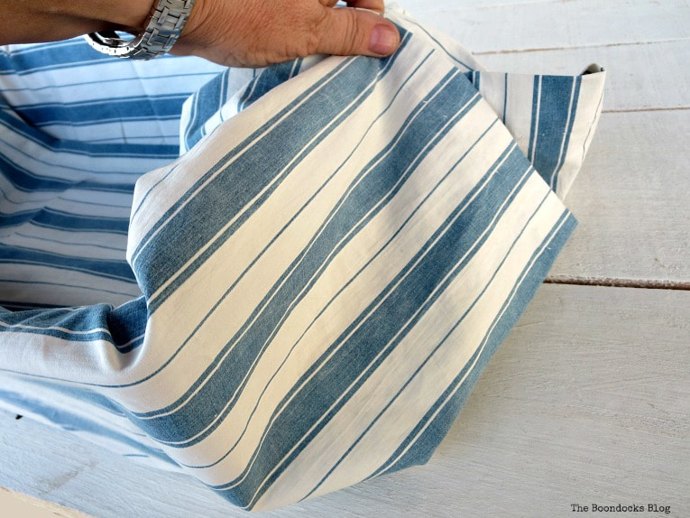folding the ends of the fabric, How to Easily Upcycle Broken Plastic Baskets www.theboondocksblog.com