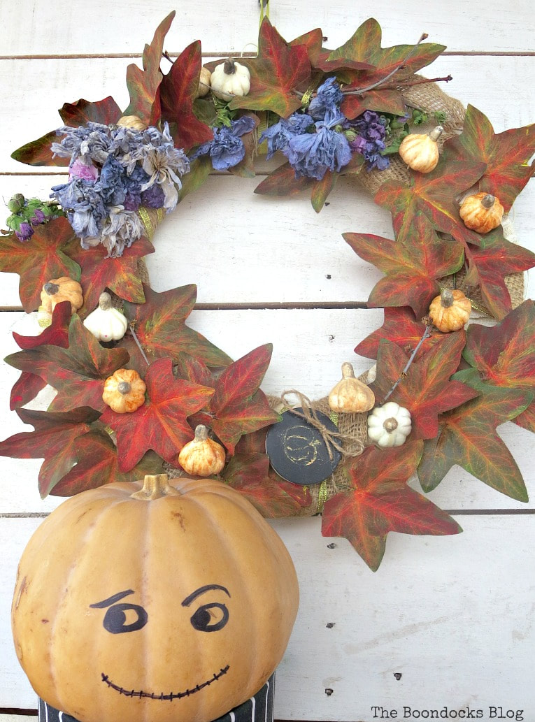 pumpkin man next to the fall wreath, How to Make a Beautiful Dollar Store Fall Wreath www.theboondocksblog.com