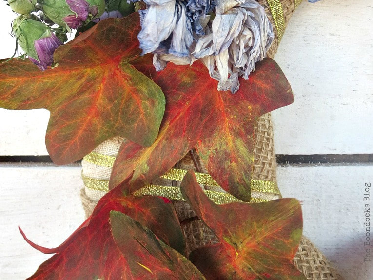 gold ribbon wrapped around wreath, How to Make a Beautiful Dollar Store Fall Wreath www.theboondocksblog.com