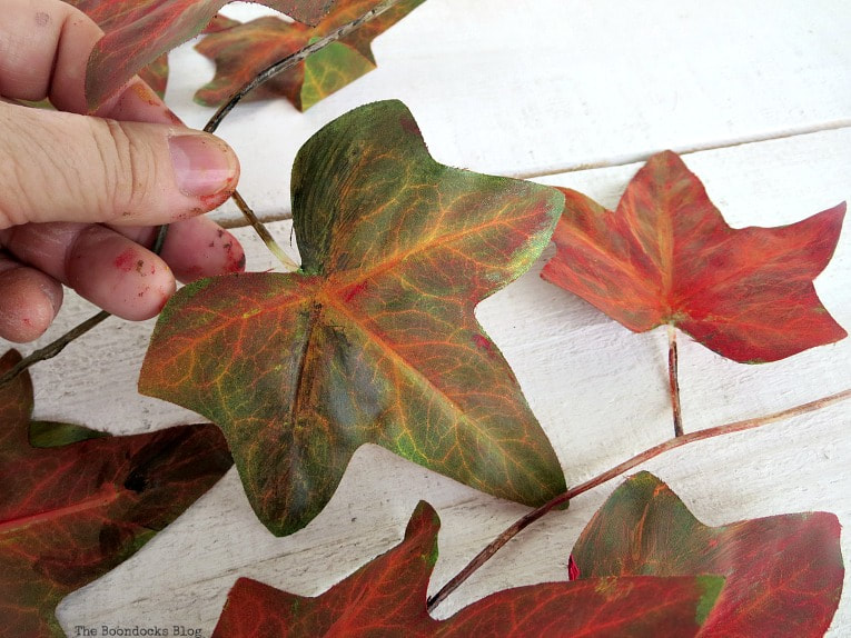 Painting the plastic leaves, How to Make a Beautiful Dollar Store Fall Wreath www.theboondocksblog.com