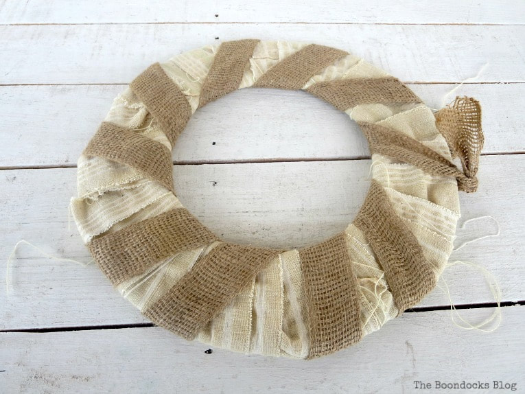 donut shaped cardboard wrapped with white fabric strips and burlap ribbon, How to Make a Beautiful Dollar Store Fall Wreath www.theboondocksblog.com