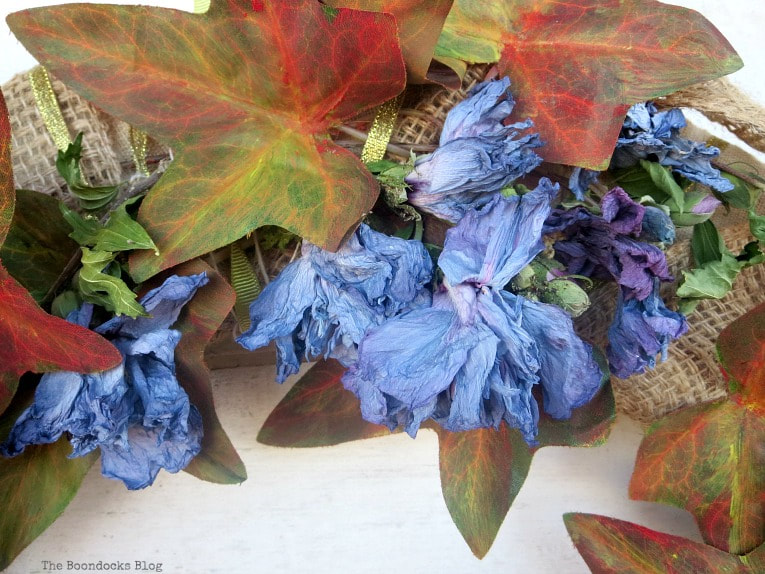 Padding dried flowers to the wreath, How to Make a Beautiful Dollar Store Fall Wreath www.theboondocksblog.com