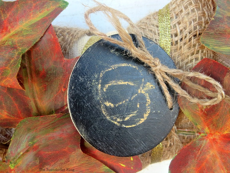 Adding a small chalkboard sign to the wreath, How to Make a Beautiful Dollar Store Fall Wreath www.theboondocksblog.com
