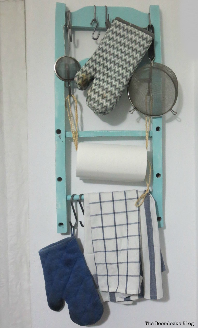 Kitchen Organizer from a chair back with towels and strainers, How to Make a Cool Kitchen Organizer from a Chair www.theboondocksblog.com