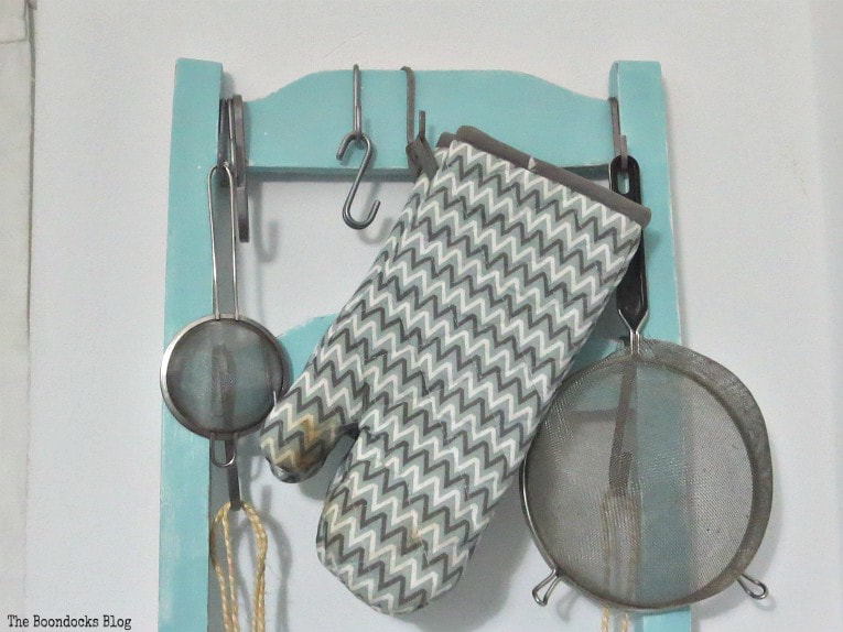 hooks are hung on top to hold utensils, How to Make a Cool Kitchen Organizer from a Chair www.theboondocksblog.com