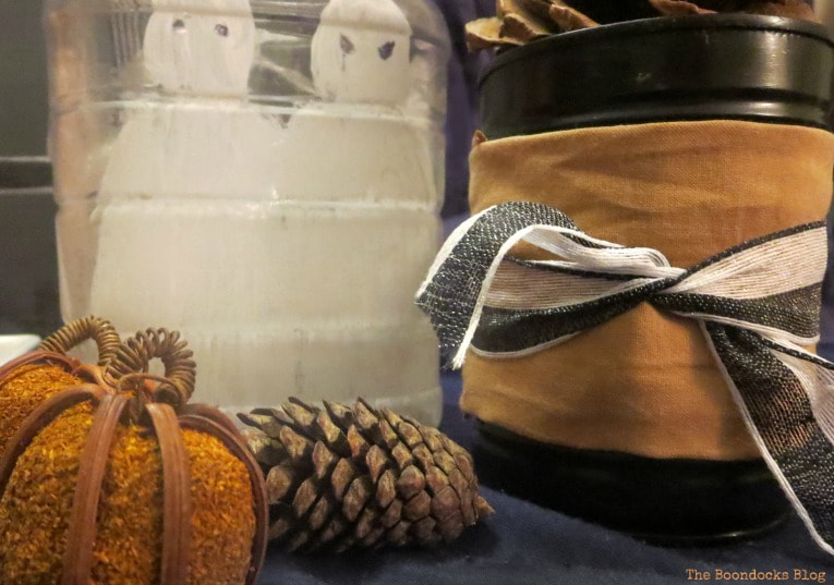 Tin cans wrapped in fabric and secured with ribbon, How to Make an Easy and Thrifty Halloween Vignette www.theboondocksblog.com