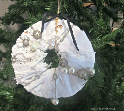 A handmade ornament wrapped using upcycled items.