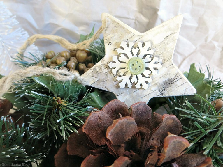 opening a hole on top and passing twine through the hole, How to Make Rustic Star Christmas Ornaments www.theboondocksblog.com