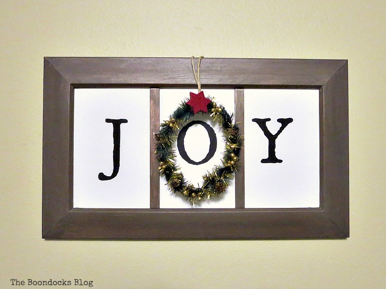 Upcycling a plastic picture frame to make it look rustic wood and adding a printable. #holidaysign #upcycledprictureframe #easycraft #christmascraft #printables #JOY How to Make Easy Wall Decor for the Holidays www.theboondocksblog.com