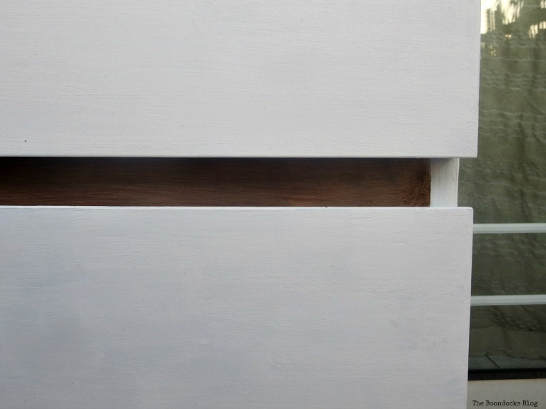 Close up of white drawers with walnut front frame of dresser.