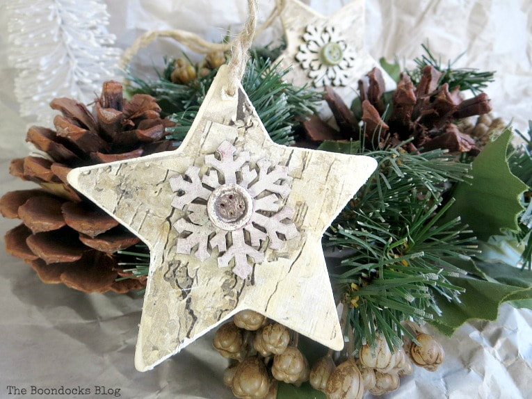 finished ornament with white snow flake and brown rustic button for farmhouse look, How to Make Rustic Star Christmas Ornaments www.theboondocksblog.com