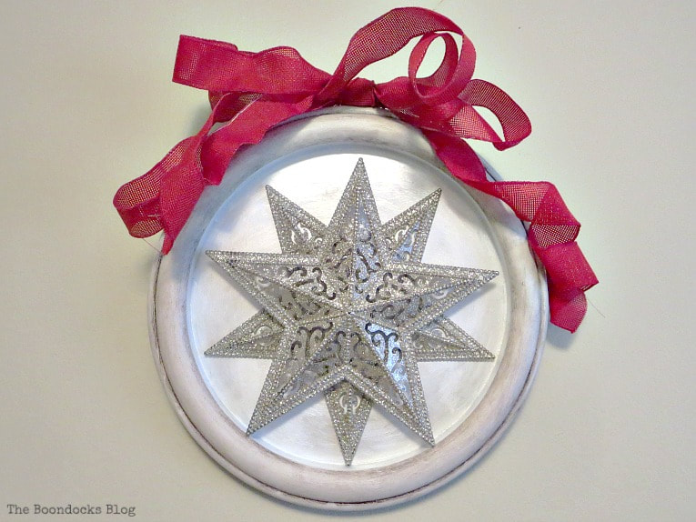 Adding a red ribbon to the top, How to Make a Christmas Craft with Dollar Store Items www.theboondocksblog.com