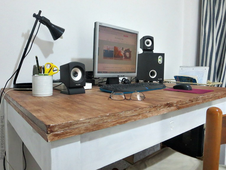 Wood desk with computer, black lamp, glasses, speakers and pen holder placed on top.