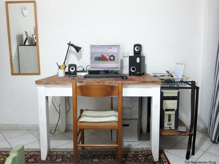 Wood desk placed beside metal table and wall mirror.