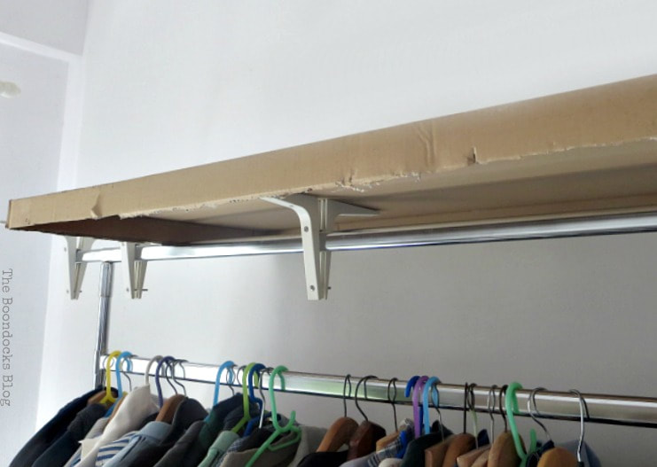 The clothes rack with brackets and cardboard on top.