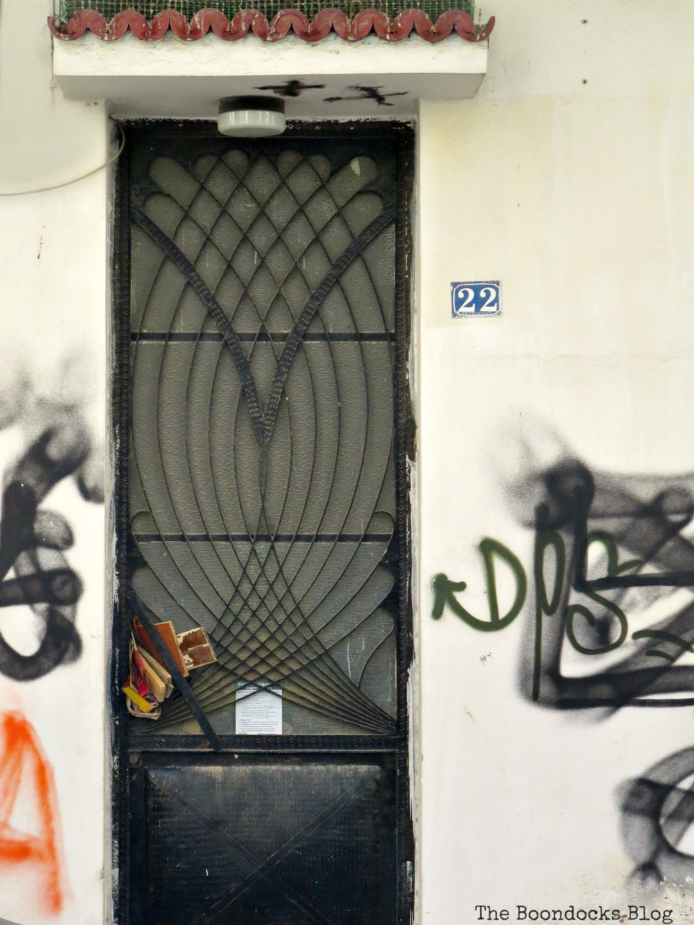 black metal door with intertwining meal arches on upper part and graffiti, Celebrating a 3 year Blogoversary with Lots of Doors www.theboondocksblog.com