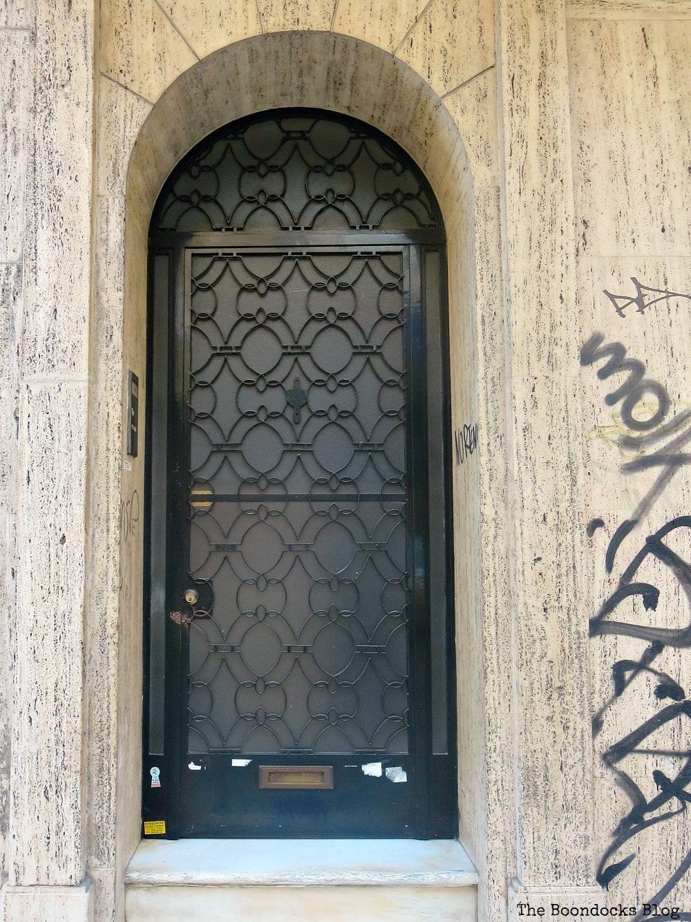 Black metal door with metal scrollwork, Celebrating a 3 year Blogoversary with Lots of Doors www.theboondocksblog.com