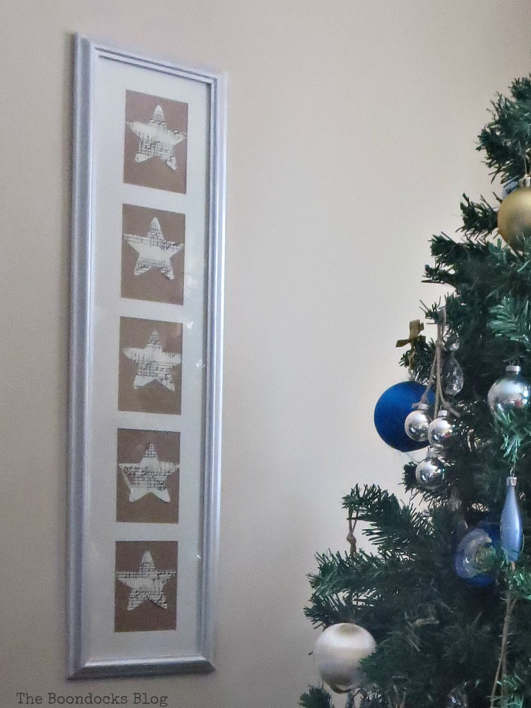 A picture frame with five openings and musical stars next to a Christmas tree.