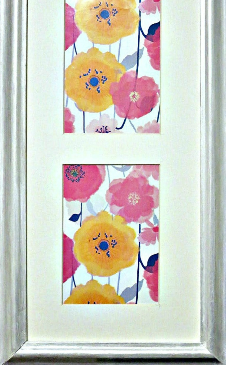 Close up of flower wrapping paper placed inside a frame to make spring artwork.
