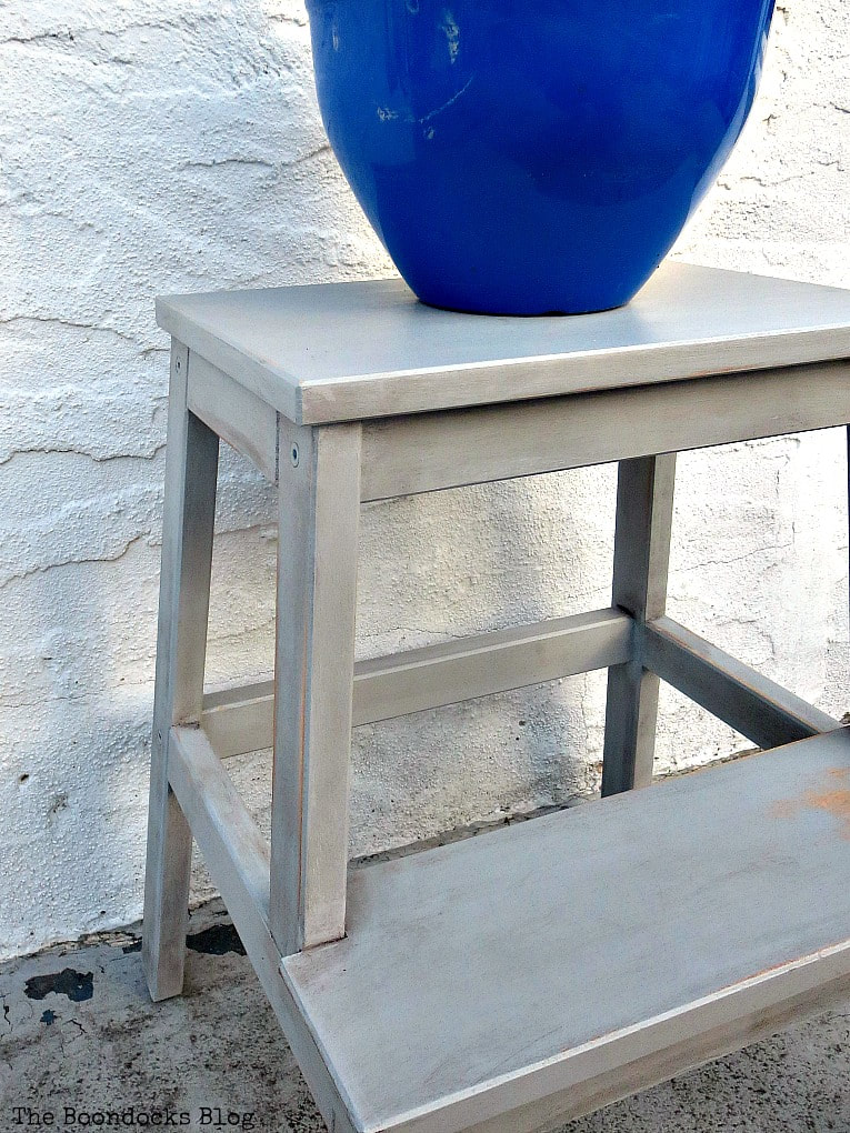 The Ikea stool, painted grey, with a  blue planter on top.