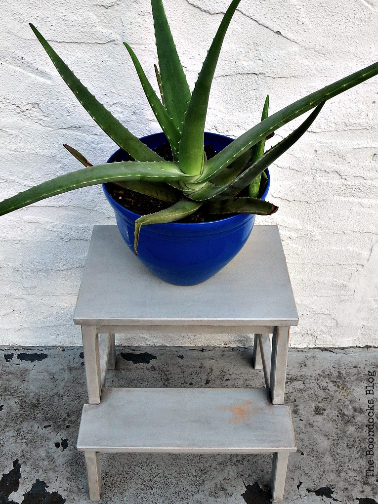 A blue planter filled with an aloe plant on top of a painted Ikea Bekvam step stool.