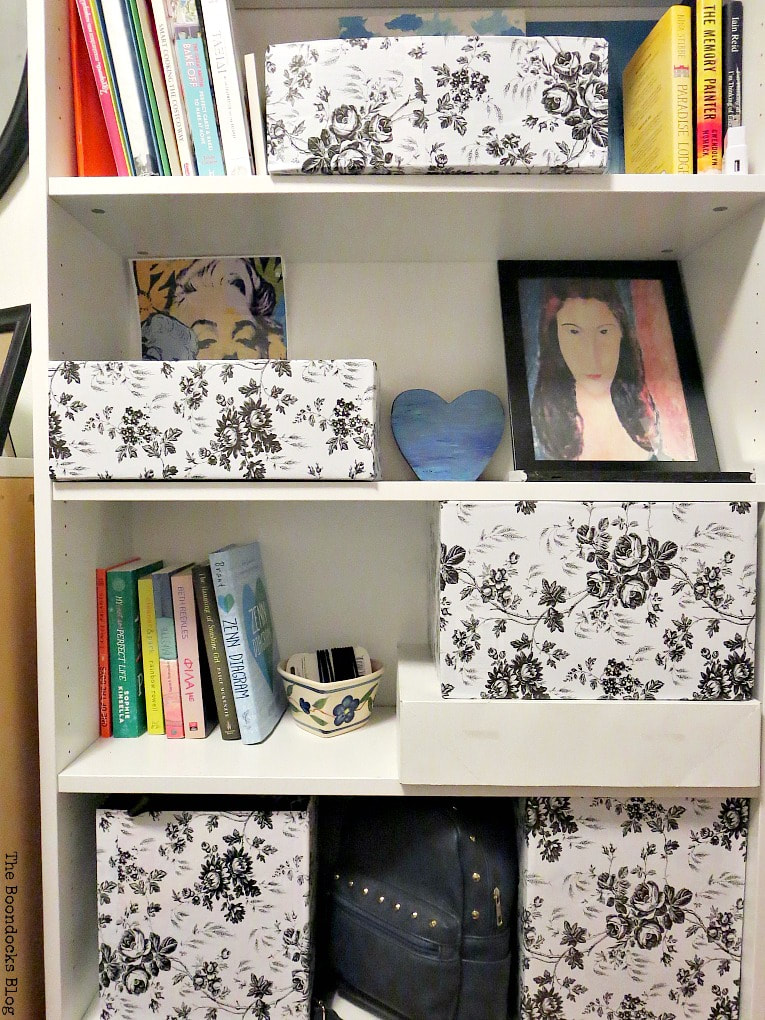 Bookcase with black and white floral covered boxes, books and artwork, A Bedframe Refresh and Progress in the Room www.theboondocksblog.com