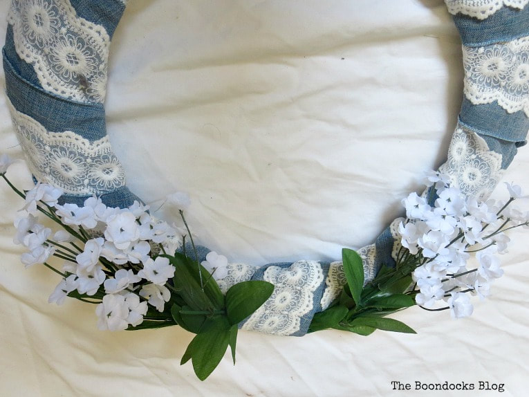 Adding the white flowers on the bottom, How to Add Color to your Home with Wreaths www.theboondocksblog.com