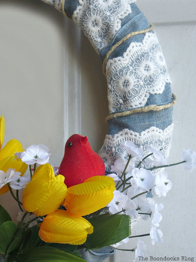 Spring wreath in front of door with flowers, ribbon and a red cardinal, How to Add Color to your Home with Wreaths www.theboondocksblog.com