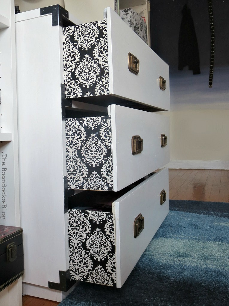 Side view of the upcylced dresser with Damask paper on the sides of drawers.
