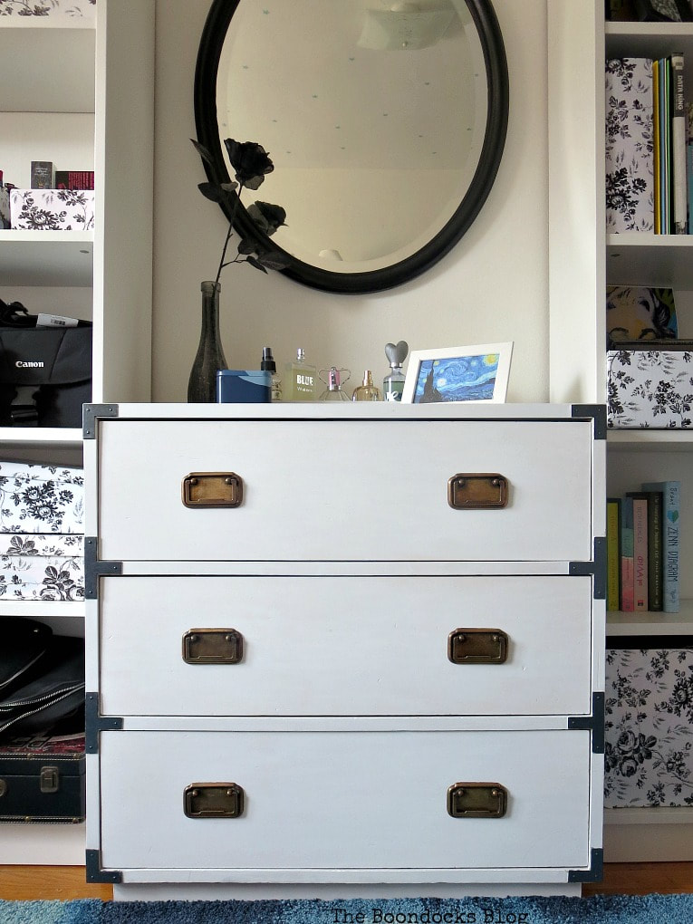 Restored white dresser flanked by two bookcases and with a black mirror hanging above it.