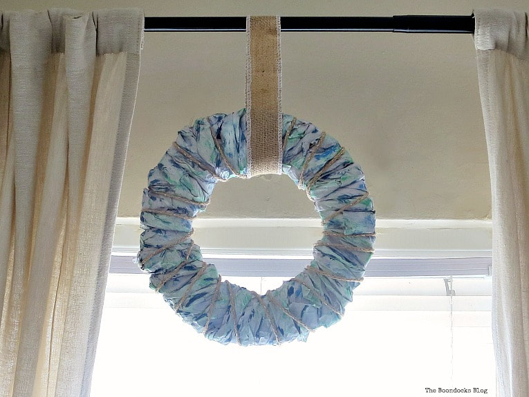 Colorful packing paper wreath hung on curtain rod.