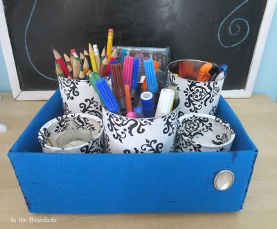 Box with tin cans as organizer