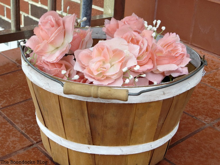 basket with faux flowers as outdoor decor, #repurposeddecor #outdoordecor #curbappeal #repurposedrubberboots #fauxflowers #easyupcycleddecor #reusingbrokenchair How to re-purpose a torn rattan chair, www.theboondocksblog.com