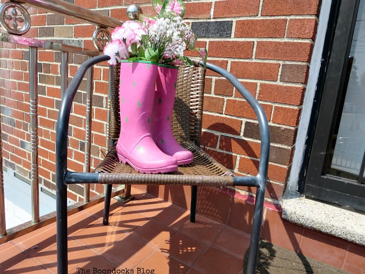 rattan chair with rubber boots and faux flowers, How to re-purpose a torn rattan chair, www.theboondocksblog.com