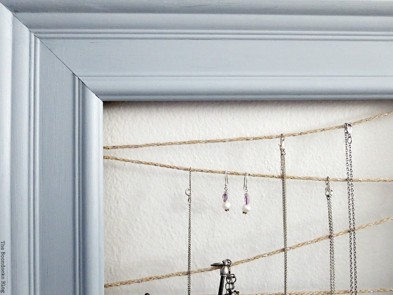 Close up of Jewelry organizer made with frame and twine, #Jewelryorganizer #repurpose #organize #frame #easyJewelryorganizer #DIYproject How to Make an Easy Frame Jewelry Organizer www.theboondocksblog.com